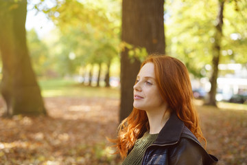 Young ginger woman standing in park on autumn day