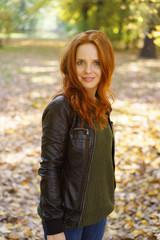 Red-haired woman standing in park on autumn day