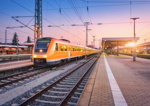 Passenger high speed train on the railway station at sunset. Urban landscape with modern commuter train on the railway platform against colorful sky at dusk. Intercity vehicle on railroad in Europe