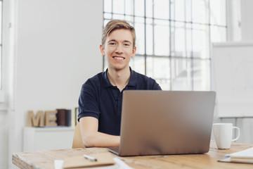junger auszubildender sitzt im büro vor dem laptop