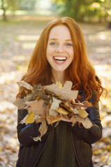 Young cheerful woman playing with leaves in park