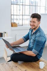 lächelnder junger mann sitzt auf dem tisch mit seinem laptop