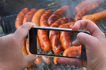 Food photography of baked sausages, meat. Photo of baked meat, shish kebabs with smartphone. Hands taking photo grilled fresh meat with smartphone