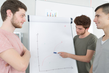 Male students looking at graph on flip chart