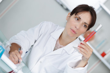 professional doctor is making notes on blood sample