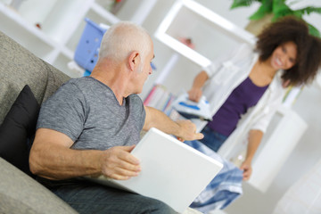 old man using laptop while talking to her assistant