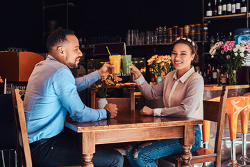 Happy beautiful African-American couple in love having a great time together in a restaurant at their dating, an attractive couple enjoying each other, holds glasses of juice.