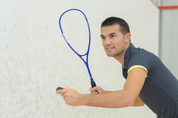 Man poised to serve playing squash