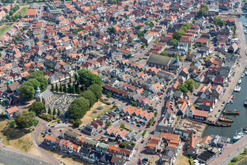 Aerial view Dutch fishing village with harbor, lighthouse and residential area
