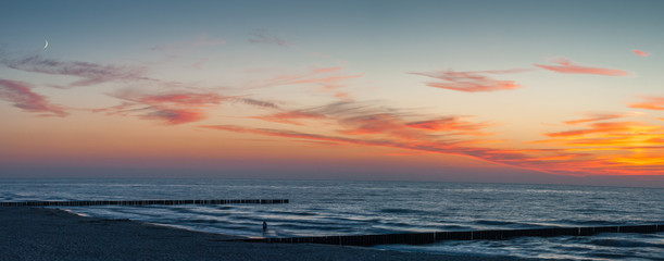 Panoramic sunset and a single person walking along the seashore