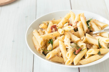 Penne with canned tuna, spinach, sun dried tomatoes and parmesan cheese served in white bowl.