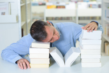 tired man sleeping on a pile of books