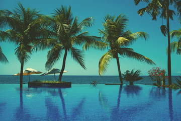 Reflection of coconut trees in turquoise color swimming pool. Beautiful wiev at a beach resort in tropics. Palm tree and luxury hotel swimming pool at vacation times. Summer, vacation, travel concept
