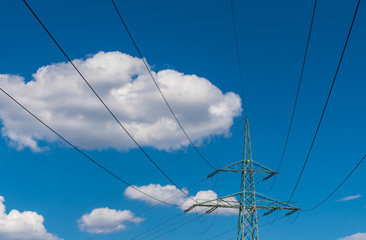Transmission tower top part on a blue sky background. Wires of power line on electricity pylon detail against beautiful heaven with white fluffy clouds. Sunny summer day. Idea of industry, ecology.
