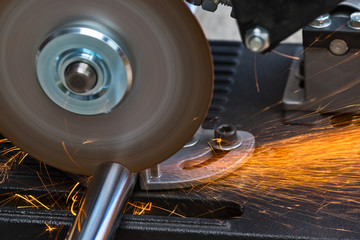 Cutting a metallic rod by a circular saw machine. Close-up of hot flying sparks when sawing a steel workpiece. Motion blur of disc with sharp blade. Idea of metal working in mechanical engineering.