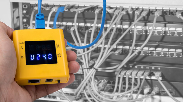 Testing of PoE on cables connected in patch panels of rack case. Human hand detail when gauging structured cabling by a yellow measuring instrument. Tester of Power over Ethernet.