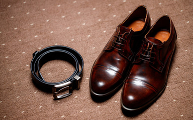 classic brown shoes and belt on wooden floor. vintage picture