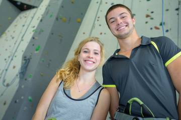 sporty male and female posing at climbing wall