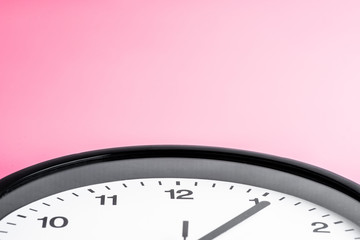 A pink wall clock on pink background Theme of Working business The concept of The time Copy space