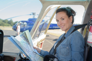 woman holding a map in the helicopter cockpit