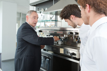 Young waiters learning how to use coffee machine