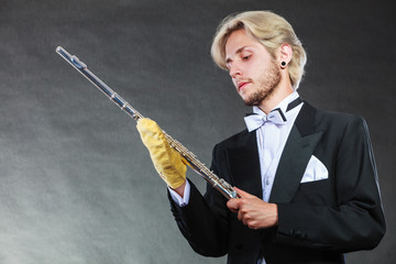 Elegantly dressed musician man cleaning flute