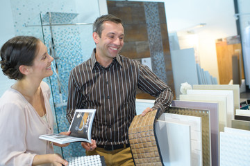 male seller advising female client with tiles samples