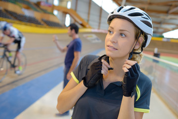 female bicycle comptetitor putting her helmet on