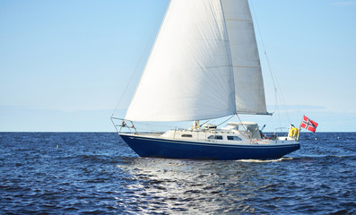 The blue yacht sailing in an open sea on a clear sunny day, Latvia