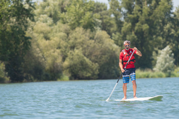 mature attractive rider contemplating nature sitting on paddle board