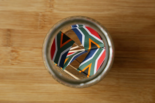 A mason jar filled with small South African flags.