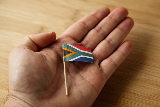 A Caucasian hand holding a small South African flag.
