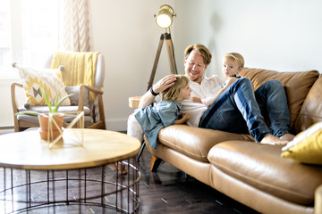 Young father with baby daughter and son on sofa at home