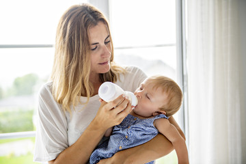 Home portrait of a baby with mother feeding her child from bottle.