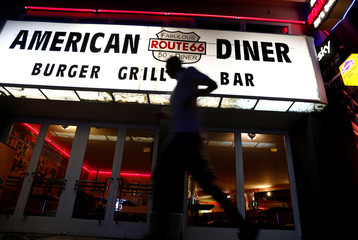"A man walks past ""Route 66 Diner"", which offers American diner food, in Berlin,"