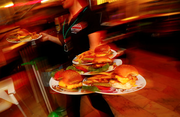"""A waitress serves hamburgers at """"Route 66 Diner"""", which offers American diner food, in Berlin"""