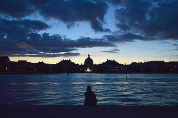 Girl looking at the sunset in Copenhagen harbor.