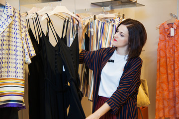 Shopping sale mall concept, woman at shop choosing clothes. Young female customer posing at clothes store