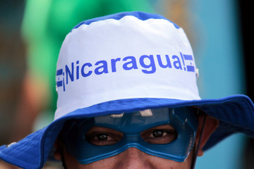 A masked anti-government protester takes part in a march to demand the release of demonstrators detained during recent protests against Nicaraguan President Daniel Ortega's government in Managua