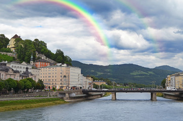 SALZBURG, AUSTRIA - JUNE 22, 2018: Picturesque view of city street on riverside and rainbow in sky
