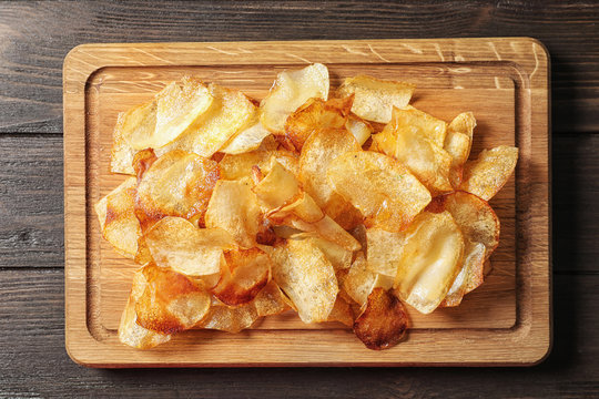 Wooden board with crispy potato chips on table, top view
