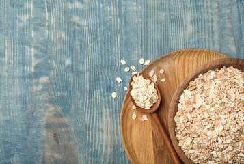 Bowl and spoon with oatmeal on wooden background, top view. Grains and cereals