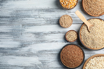 Flat lay composition with different types of grains and cereals on wooden background