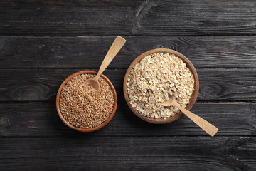 Bowls with oatmeal and wheat on wooden background, top view. Grains and cereals