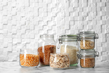 Jars with different cereal grains on marble table