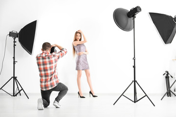 Young woman posing for professional photographer on white background in studio