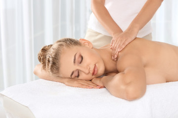 Relaxed woman receiving neck massage in wellness center