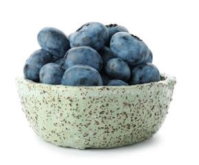 Bowl full of fresh ripe blueberries on white background