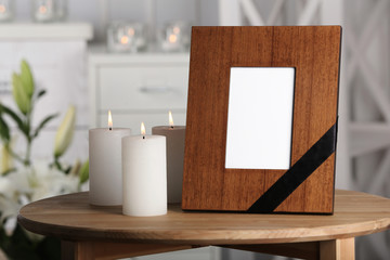 Funeral photo frame with black ribbon and burning candles on table, indoors