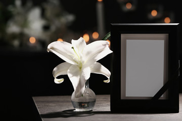 Funeral photo frame with black ribbon and lily on table in dark room